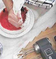 С помощью кондитерского мешка делаем белые цветы по кругу торта.